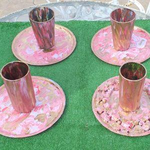 Τέσσερα χειροποίητα μεταλλικά πιατάκια, μαζί με τέσσερα ποτήρια, ζωγραφισμένα στο χέρι, σε ροζ χρώμα, ομορφαίνουν το τραπέζι σας.