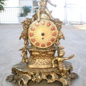 Επιτραπέζιο Γαλλικό μεταλλικό σπάνιο ρολόι σε χρυσό, σκαλιστό με αγαλματίδια, σε μαρμάρινη βάση, το ρολόι λειτουργεί κανονικά. έχει διαστάσεις 40χ40χ20 εκ.