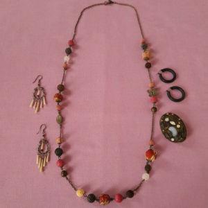 Ένα κολιέ με δύο ζευγάρια σκουλαρίκια και μία καρφίτσα.