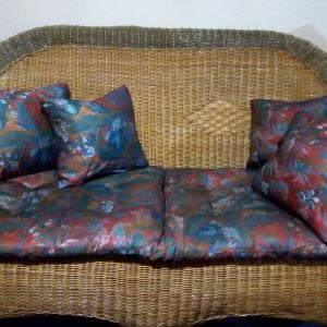 Σαλονάκι ψάθινο, διθέσιος καναπές, δύο πολυθρόνες, οβάλ διόροφο τραπέζι, γωνιακό στρόγγυλο τραπεζάκι, μικρό μπαουλάκι-κομοδίνο και γωνιακή ραφιέρα