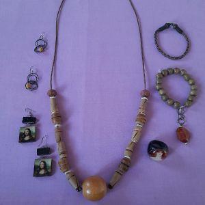 Κολιέ με ξύλινες πέτρες, δύο βραχιόλια και δακτυλίδι, καθώς και δύο ζευγάρια σκουλαρίκια δουλεμένα με ξύλο, ως δώρο.