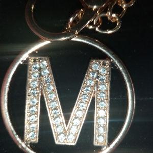 μπρελόκ χρυσό με το γράμμα Μ και φουντακι ροζ