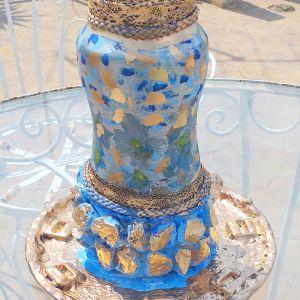 Βάζο μαζί με πιάτο, ζωγραφισμένα στο χέρι, με πετραδάκια και διάφορα διακοσμητικά. Το βάζο έχει ύψος 23 εκατοστά και το πιάτο έχει διάμετρο 21 εκατοστά.