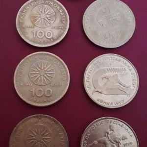 Παλαιά, ελληνικά συλλεκτικά νομίσματα, των εκατό δραχμών με τον Μέγα Αλέξανδρο και τον Ήλιο της Βεργίνας και από το παγκόσμιο πρωτάθλημα στίβου και ελληνορωμαϊκής  πάλης.